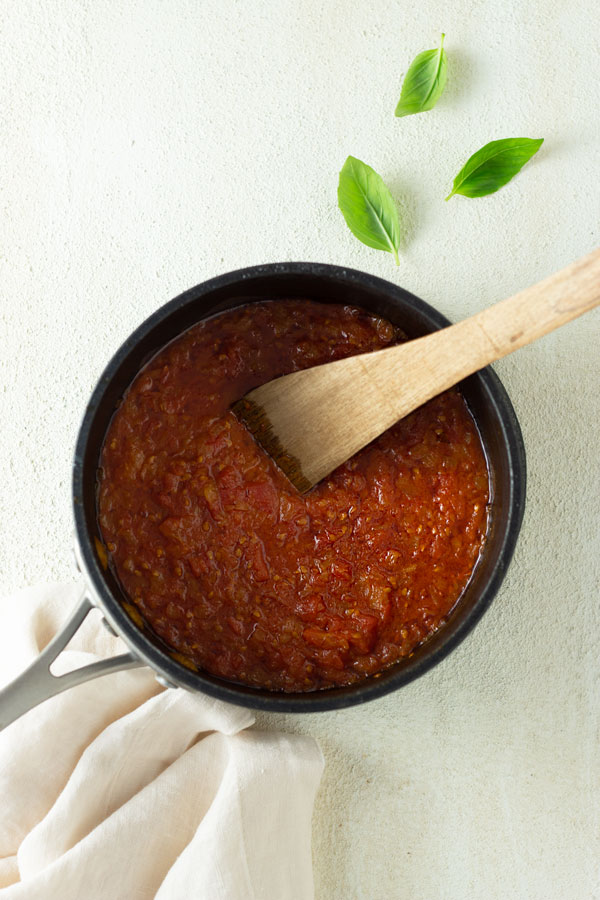 Overhead view of a pot of fresh tomato sauce being stirred by a wooden spoon on an off white textured surface surrounded by fresh basil leaves and an off white dish towel.
