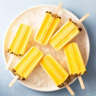 Overhead shot of Mango Lassi Popsicles with pistachios on ice on a white plate on a bright blue, textured background.