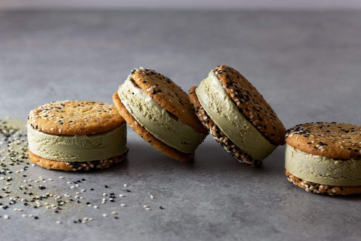 Straight on shot of a group of matcha green tea ice cream sandwiches with sesame tahini cookies leaning against each other on a light grey surface surrounded by black and white sesame seeds and matcha powder.