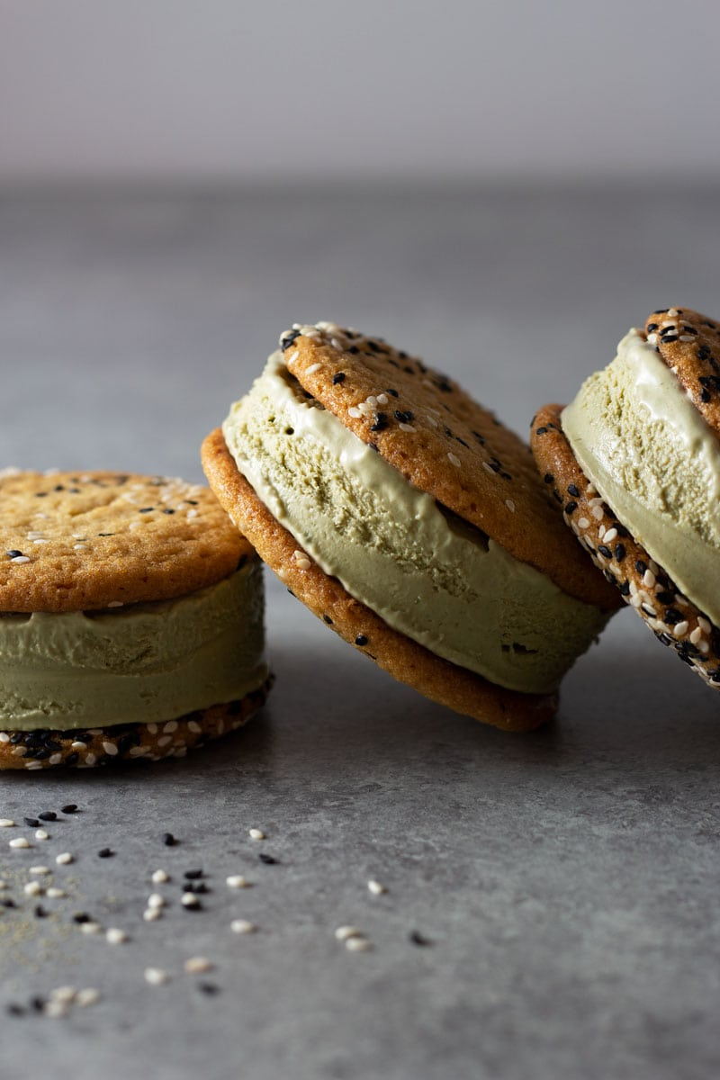 Straight on shot of matcha green tea ice cream sandwiches with sesame tahini cookies leaning on eachother on a light grey surface surrounded by black and white sesame seeds and matcha powder.