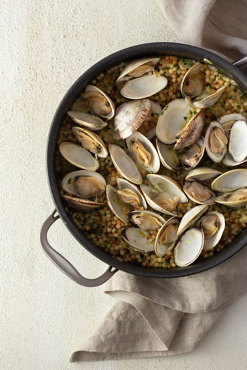 Overhead shot of a pan of fregola pasta with clams surrounded by a neutral colored towel on a light, cream colored, textured plaster surface.