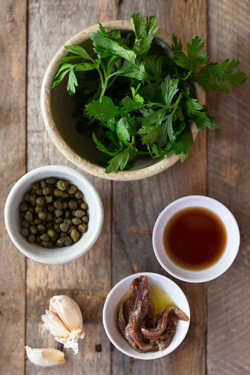 An arrangement of bowls of parsley, capers, sherry vinegar and anchovies, and a few cloves of garlic for an Italian salsa verde on a light, rustic wood surface.
