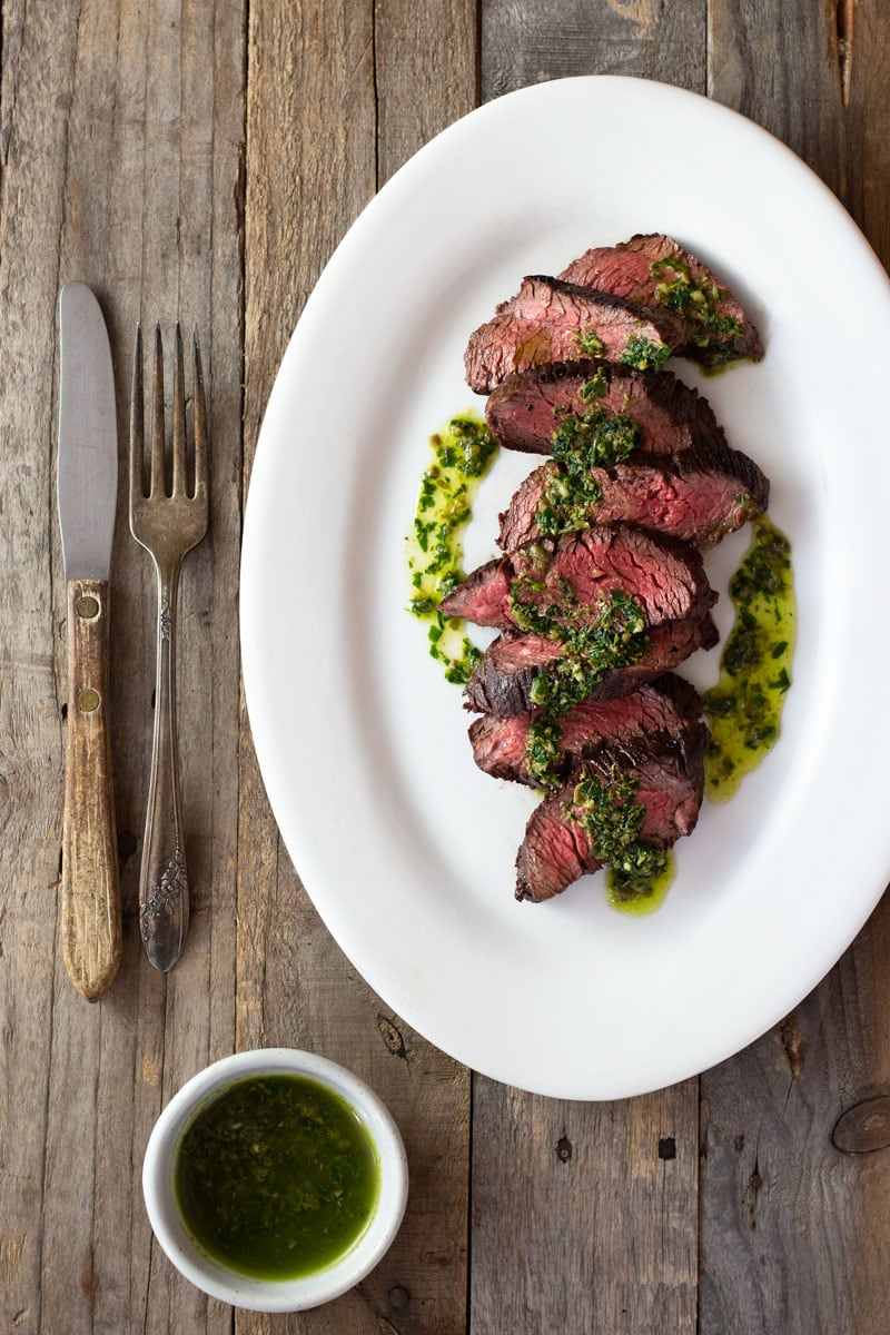 Overhead shot of sliced hanger steak drizzled in an Italian salsa verde on a light, rustic wood surface with rustic utensils and a small bowl of salsa verde.