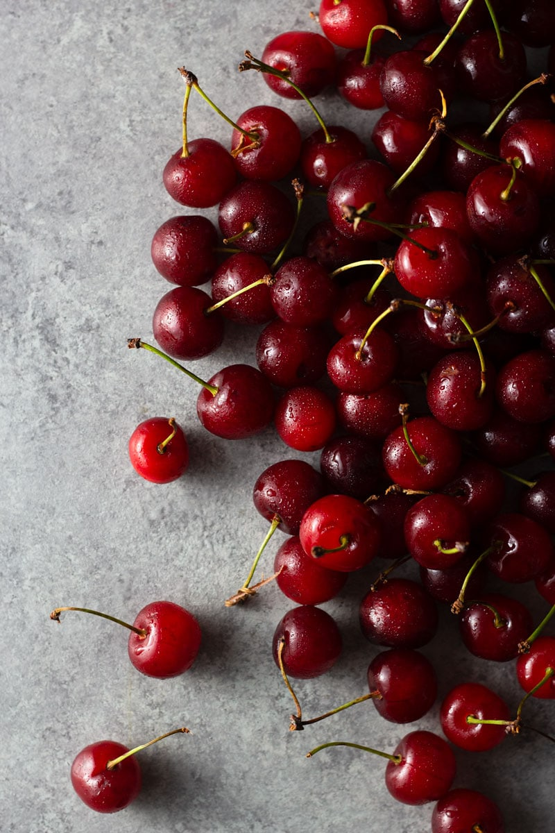 Overhead shot of a large cluster of fresh sour cherries on a light grey textured surface.