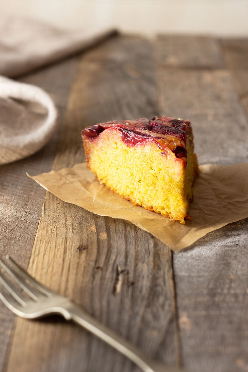 Straight on shot of a slice of Polenta (cornmeal) Plum Upside Down Cake on a square of brown parchment surrounded by a beige dish towel and rustic fork on a light grey, wood surface.