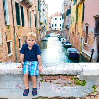 boy in front of canals in Venice