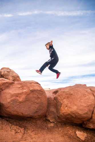 boy jumping on red rocks