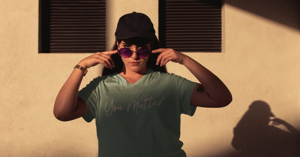 A female wearing a mint green you matter shirt with a hat and sunglasses