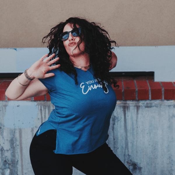 A woman with black curly hair wearing a You Are Enough Classic Fit TShirt in Indigo