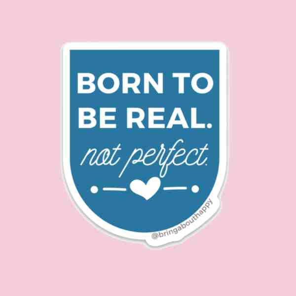 A blue badge sticker on a pink background, the sticker says Born to Be Real Not Perfect
