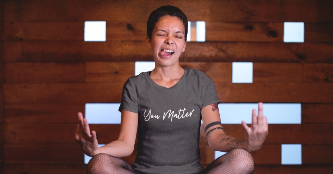 A woman making a silly face while meditating with a heavy metal gray you matter shirt on
