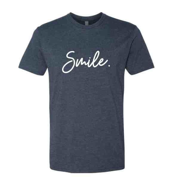 An indigo blue shirt with Smile written in white cursive font