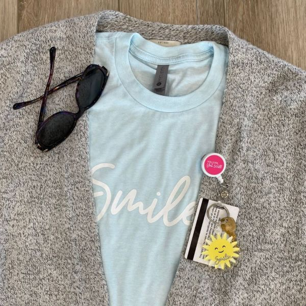 Image of a sweater and shirt with badge reel including badge and keychain