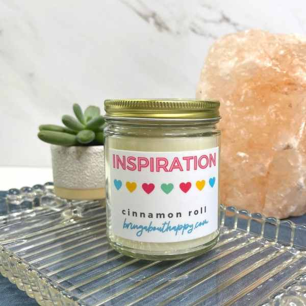 Inspiration candle with gold twist lid sitting next to a small plant and Himalayan salt rock