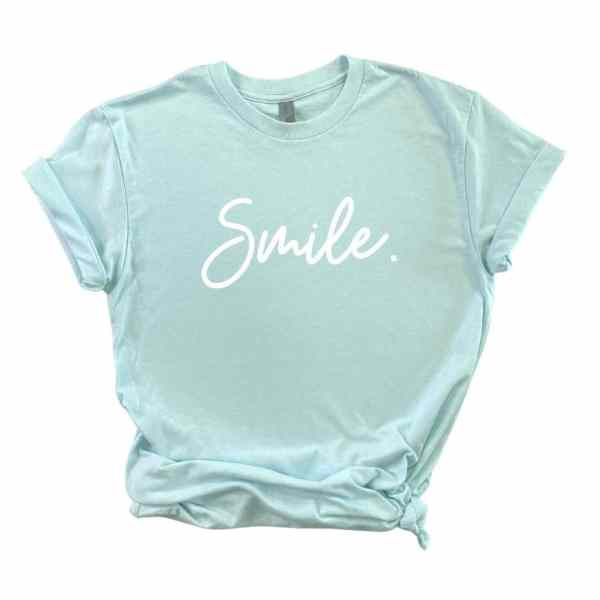 Light blue shirt with smile written in white cursive font