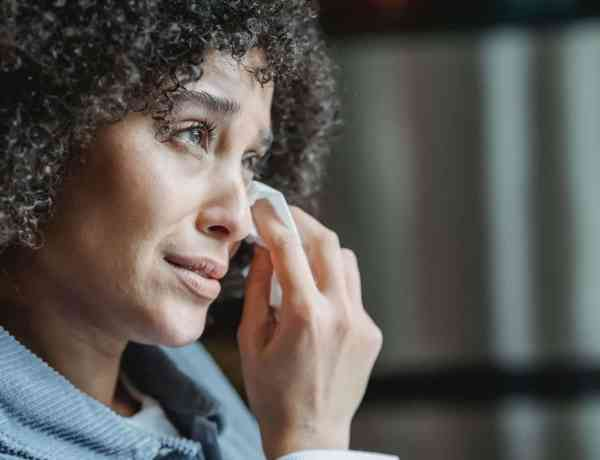 crying ethnic female wiping tears with napkin