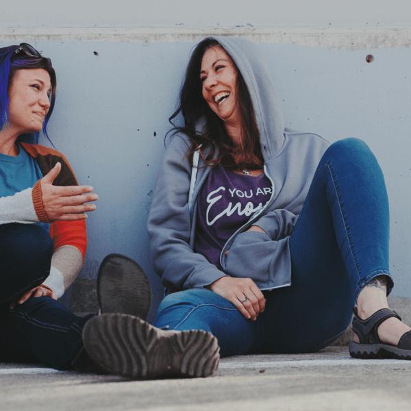 Two women talking and laughing one wearing a zip hoodie sweatshirt in mink gray