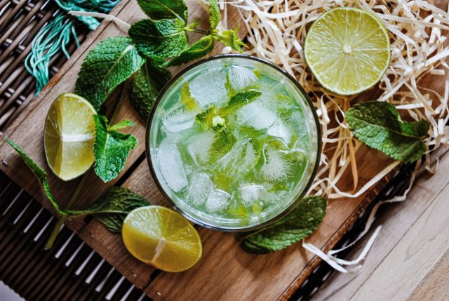 A Mojito Cocktail on a serving board surrounded by lemon slices