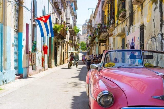 A Pink car down a narrow street in Cub