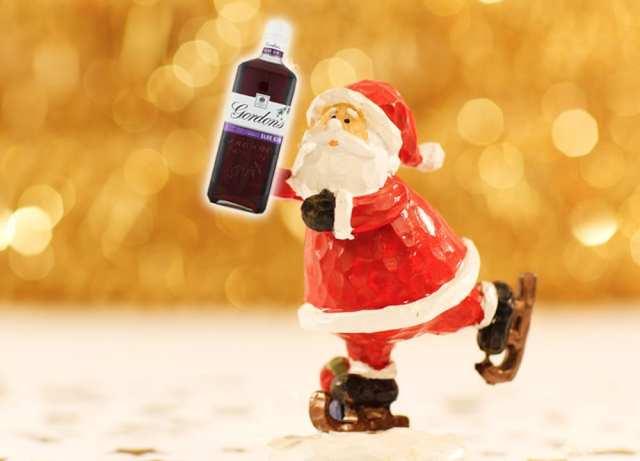 Santa holding a bottle of Sloe Gin