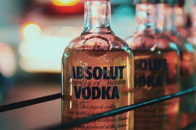 A bottle of Absolut Vodka on a bar backlit by ambient light