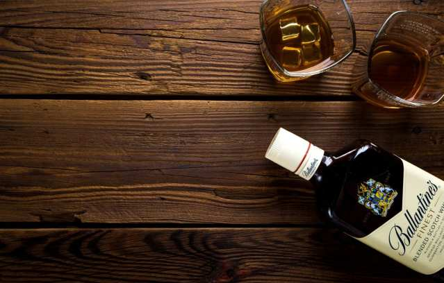 A bottle of whisky lying down on a wooden table