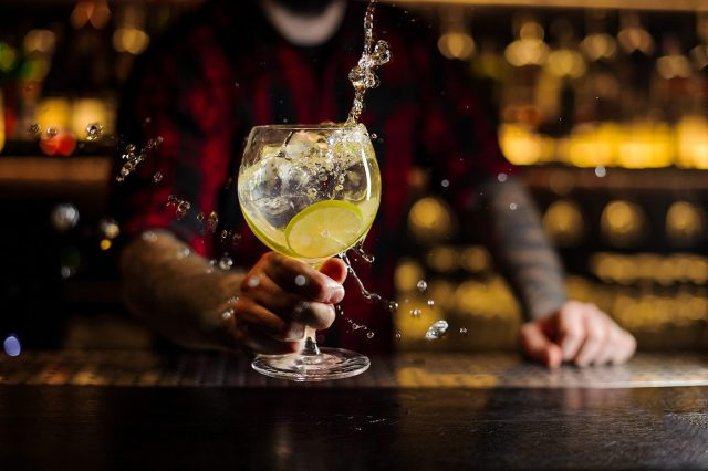 A Bartender swilling gin & tonic with a slice of lemon