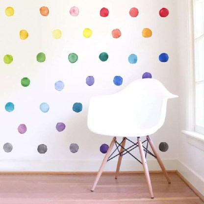 Multi coloured dot stickers on a white wall with white chair with timber legs on timber floor