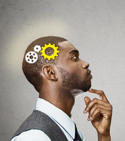 Side view portrait young business man thinking deciding finger on chin looking up gear mechanism over head isolated grey wall background