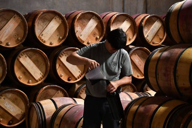 An employee pours wine into bottles as he prepares samples in the wine cellar of Chateau Margaux on June 11, 2018 in Margaux, near Bordeaux, western France. - Chateau Margaux is one of the « first Grand Cru Classe » according to an official classification of 1855 Bordeaux Wines. (Photo by GEORGES GOBET / AFP) (Photo credit should read GEORGES GOBET/AFP via Getty Images)