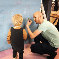 Illustrator Dave Bain gives this nipper some tips at Doodle Day