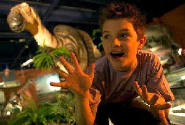 Boy next to life sized exhibit at Dinosaur Isle, Sandown, Isle of Wight, England.