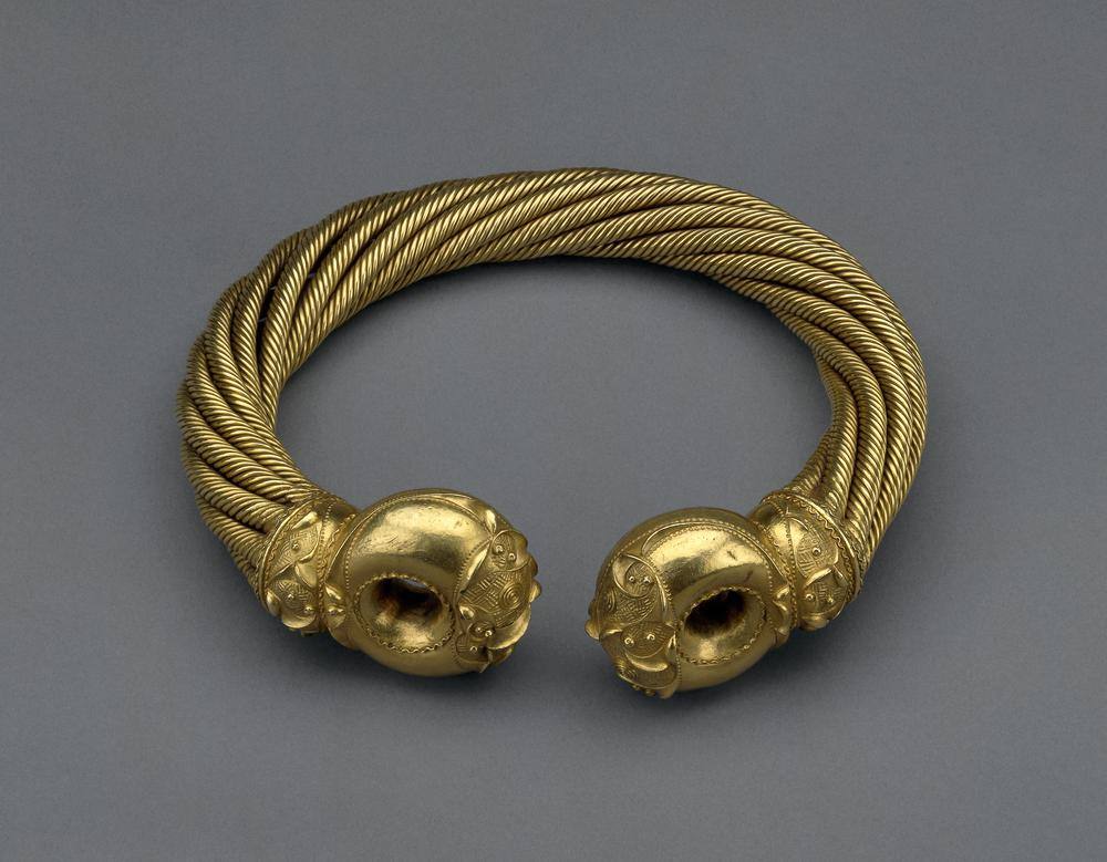 Electrum torc with ornamented terminals. The torc is made from just over a kilogram of gold mixed with silver. It is made from sixty-four threads. Each thread is 1.9mm wide. Eight threads were twisted together at a time to make 8 separate ropes of metal. These were then twisted around each to make the final torc. The ends of the torc were cast in moulds. The hollow ends were then welded onto the ropes. The terminals are ornamented with embossed ridges, contrasting with areas filled by chased 'basket-work'.