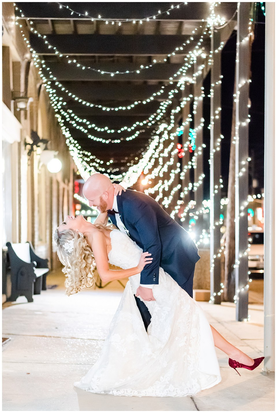 couple on wedding day on a sidewalk with string lights behind them