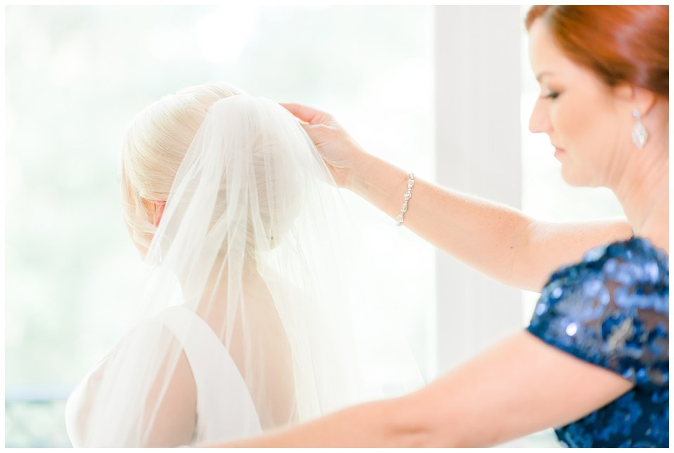 brides mom putting her veil on