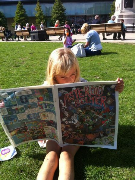 A child sat on the grass reading Asteroid Belter
