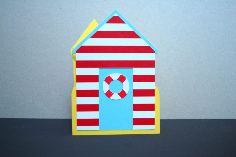 Beach Hut card, pastel blue with red stripes, front view.