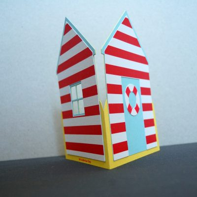 Beach Hut card, pastel blue with red stripes, side view.