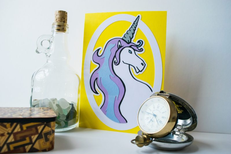 Layered paper cut Unicorn Greetings Card, on yellow card with a metallic horn and pastel blue and lilac layered mane.
