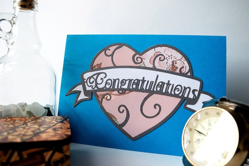 Layered paper cut Art Nouveau Congratulations Card in ocean blue with a pink patterned heart.