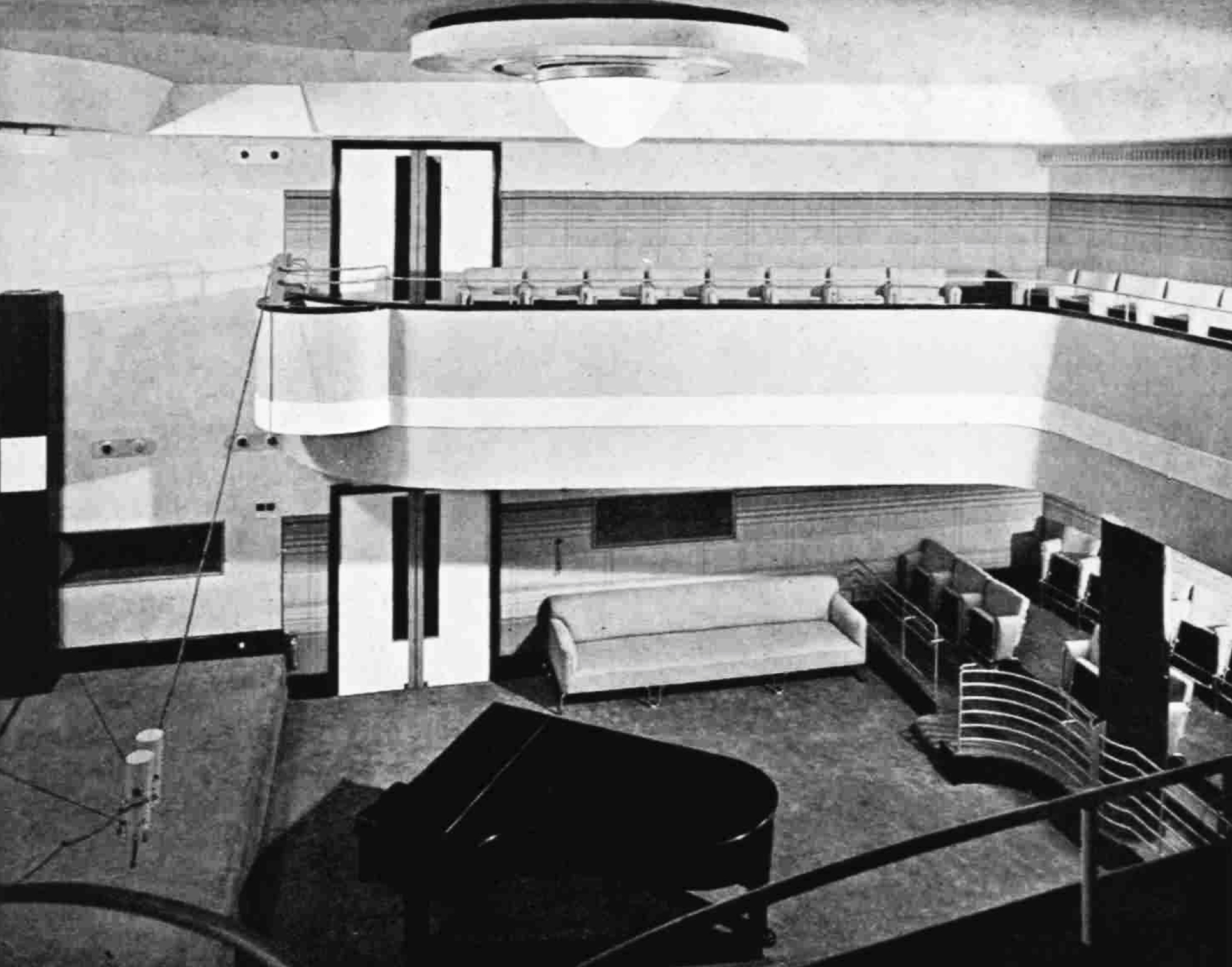 Looking down into a studio with a sofa and a piano