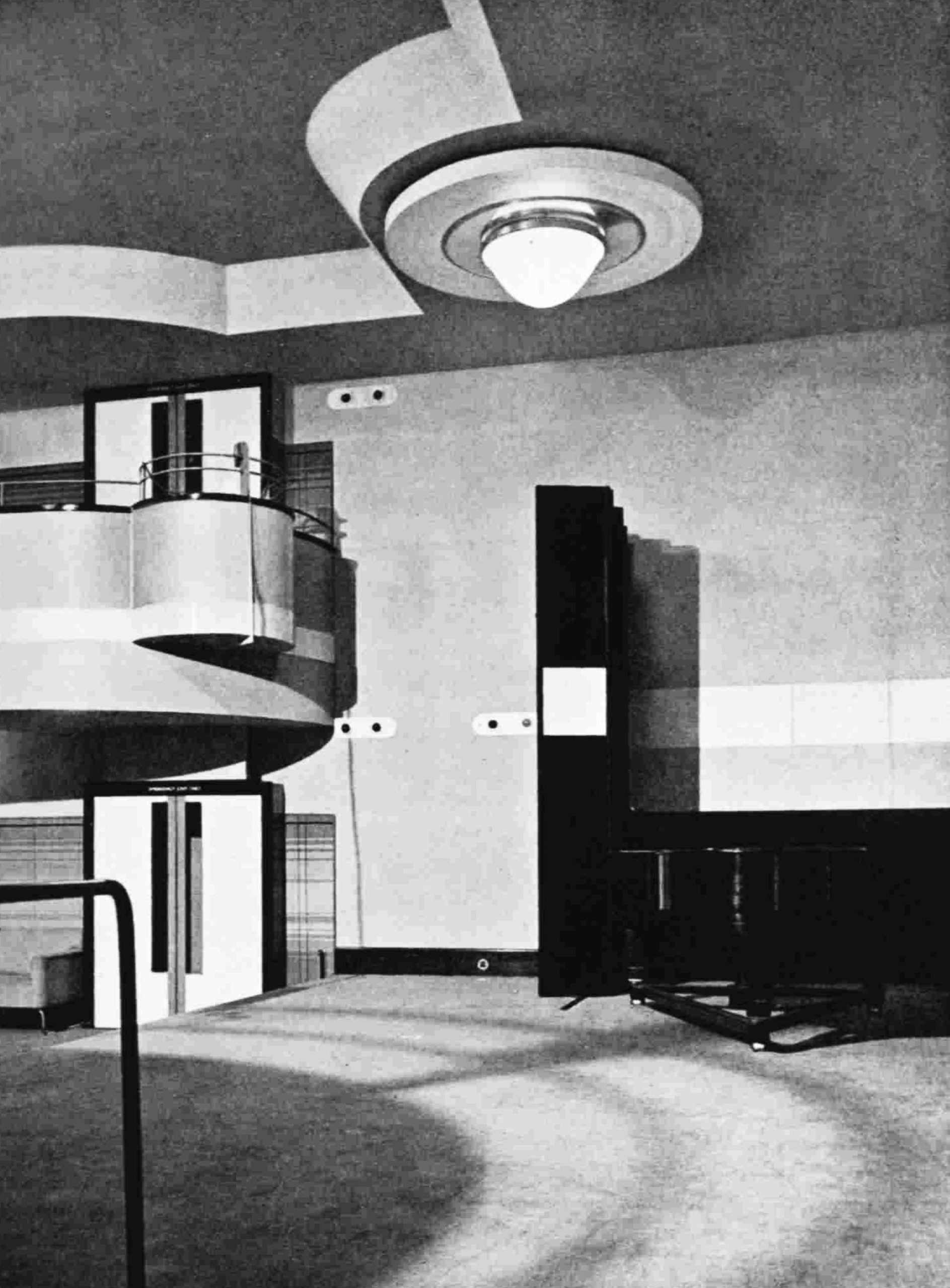 A view across a studio, with a large circular central light and a curved balcony