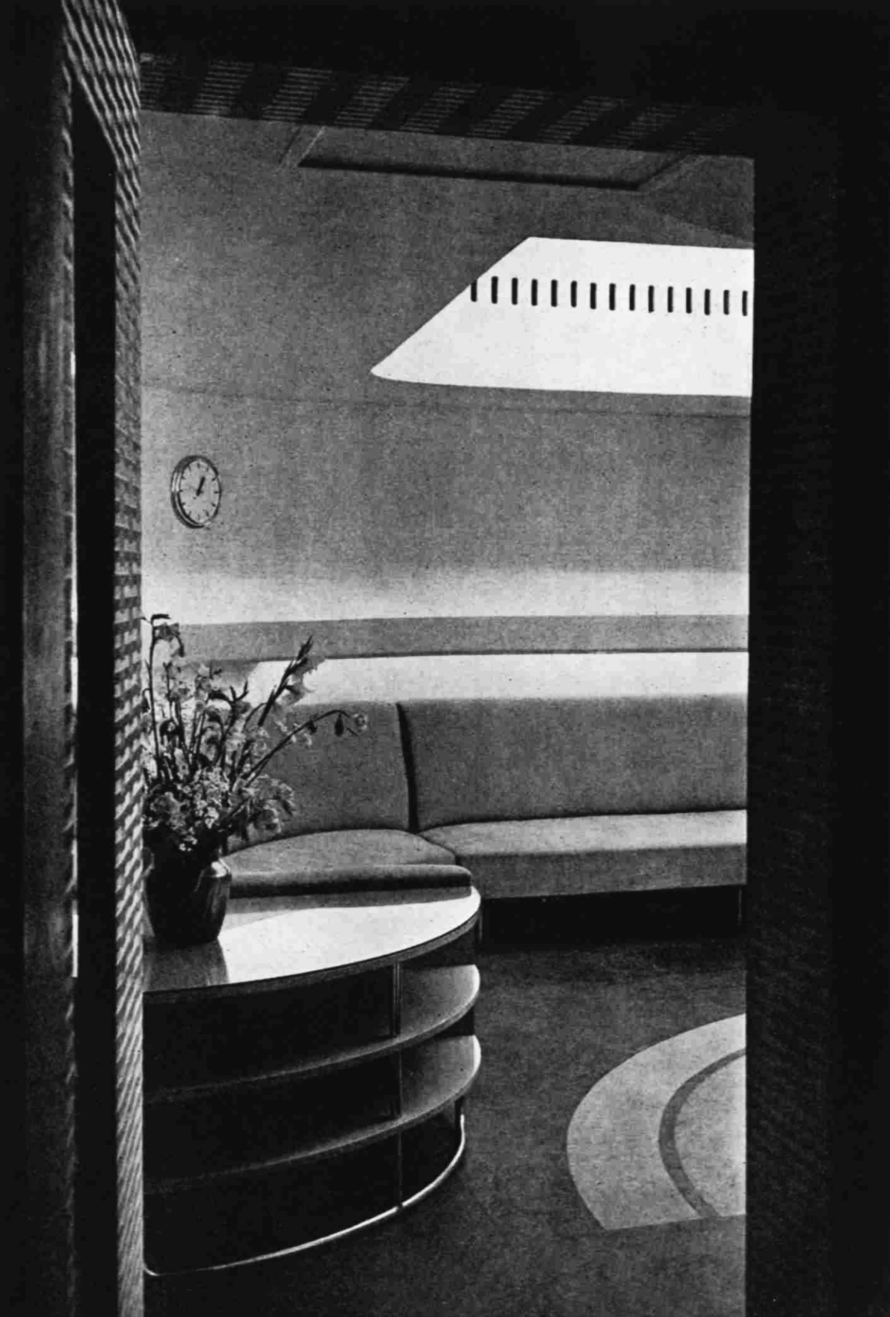 Looking in through a door at a curved shelving unit and a fitted sofa along the back wall