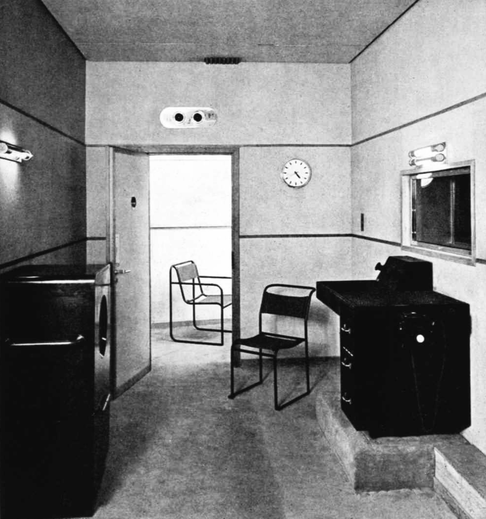 A control desk and a large speaker with an internal window to a studio; a door stands open with a single chair in the room beyond