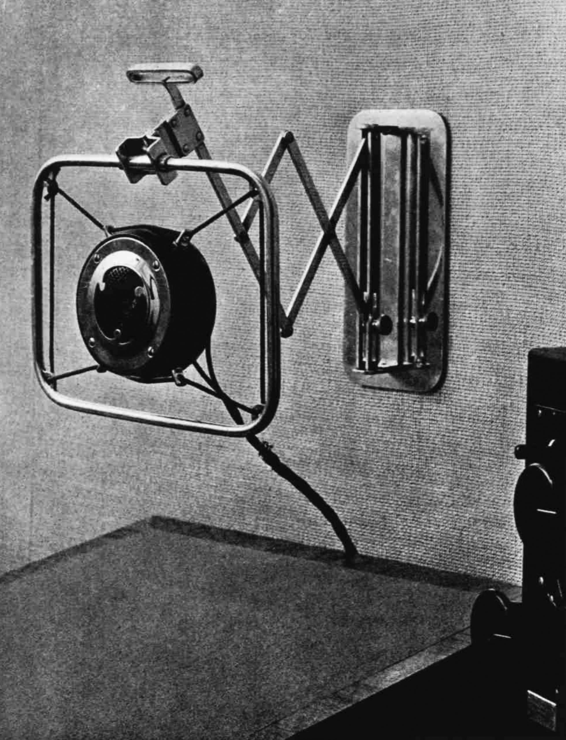 A round microphone in a square frame, bouncing from the wall on a scissor-like projection