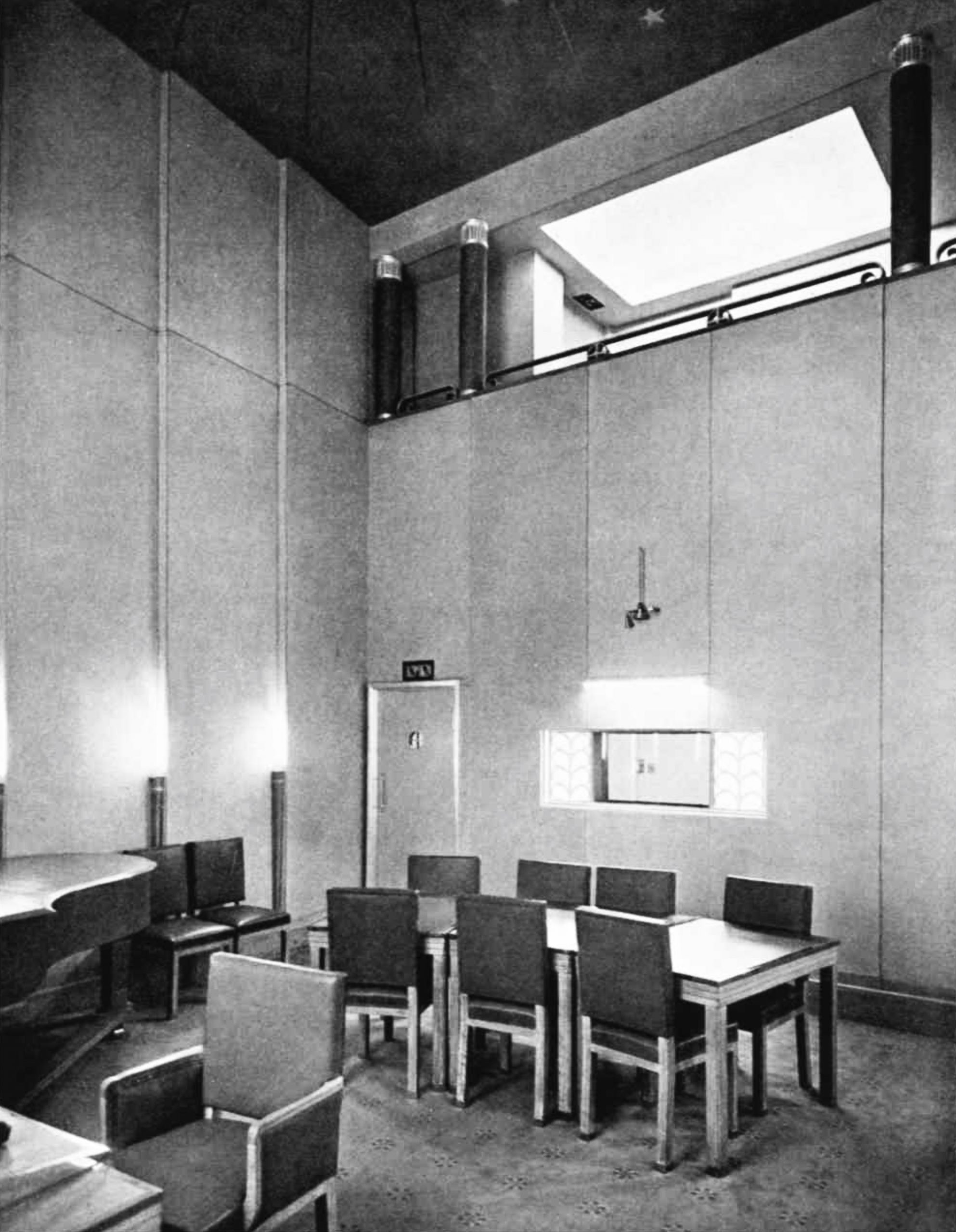 A tall room with a piano, desk and many chairs