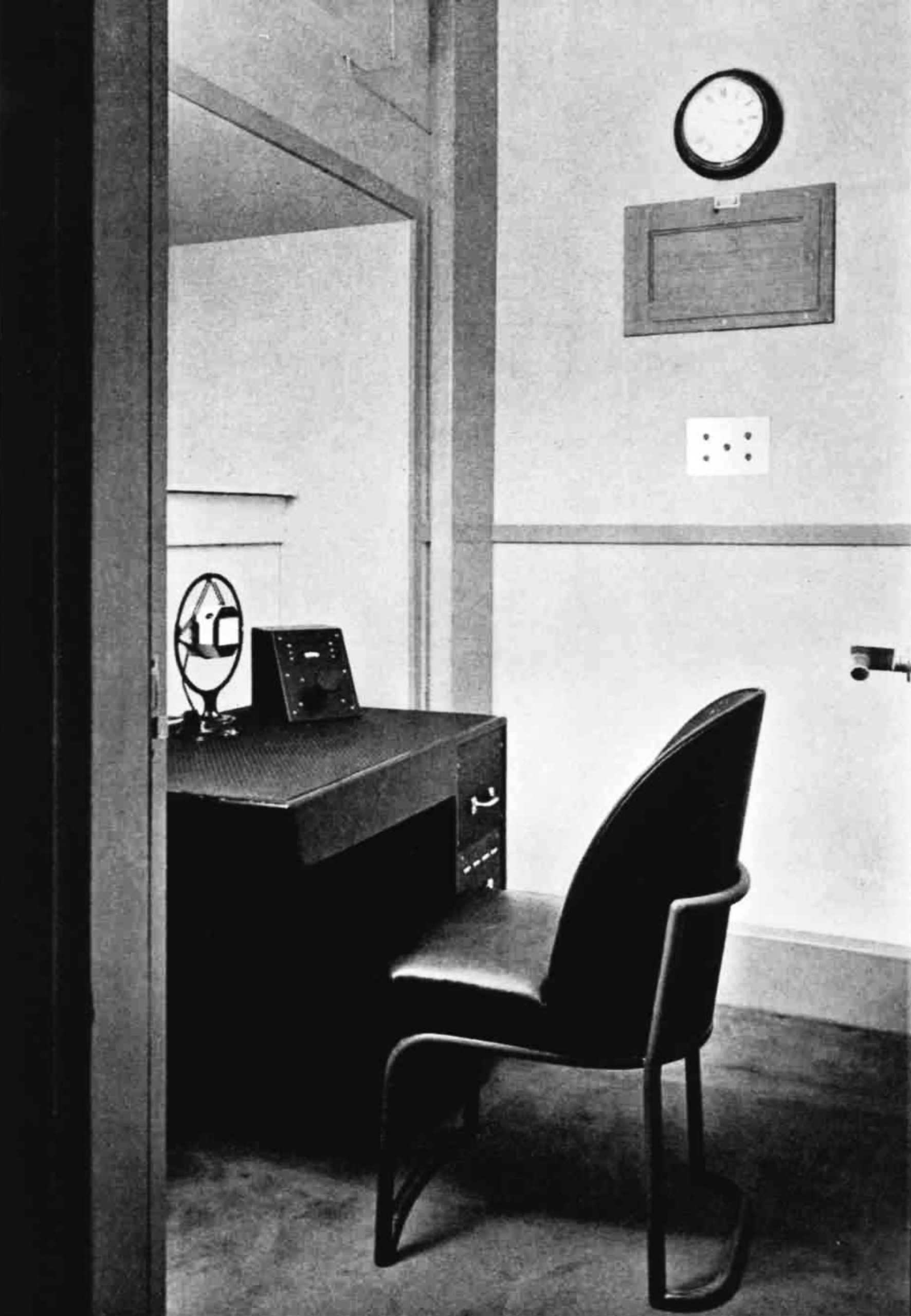 A small room with a chair, a desk and a microphone