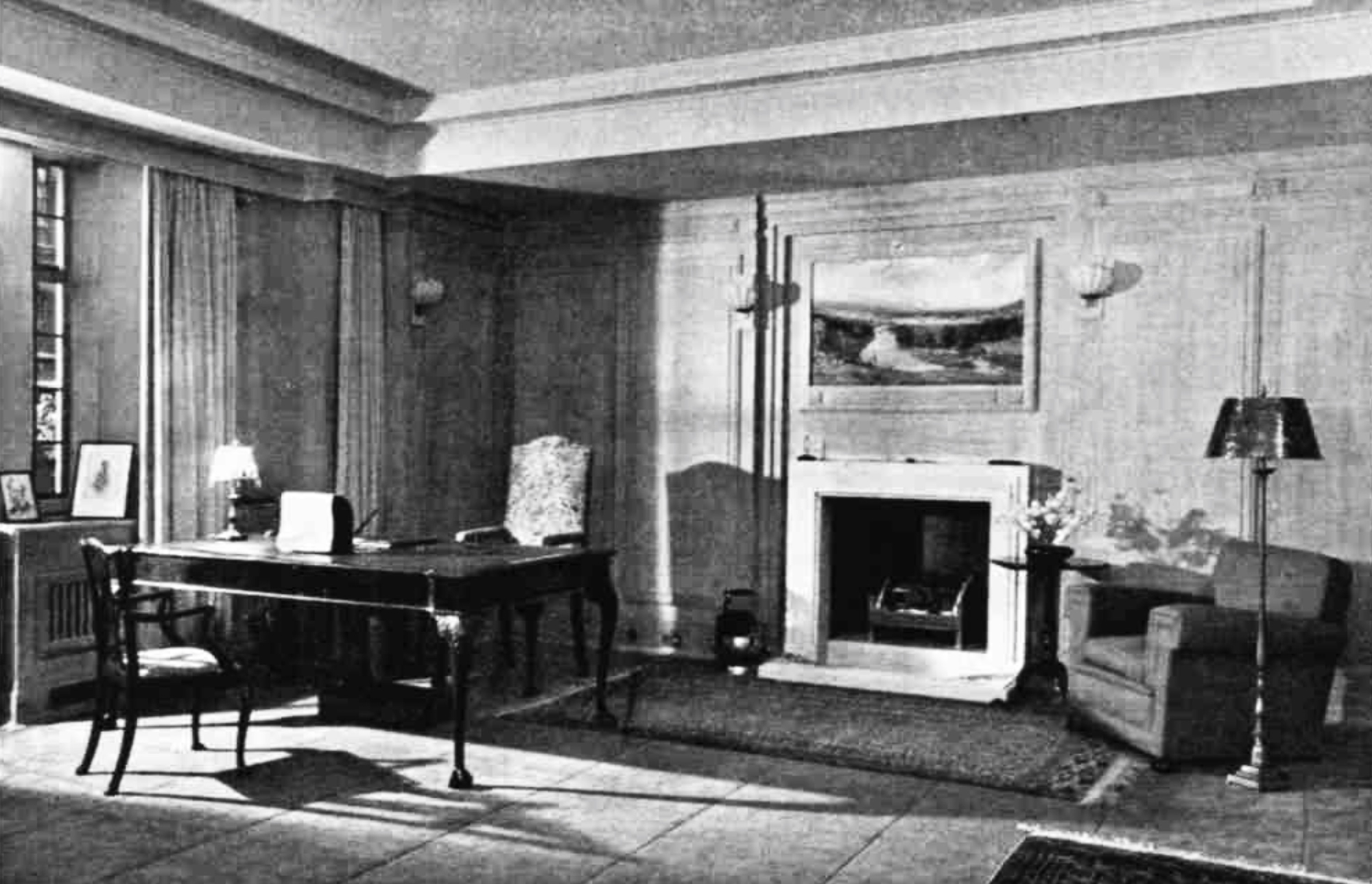 A room with wooden walls, a fireplace and an ornate desk with one commanding chair and one basic chair