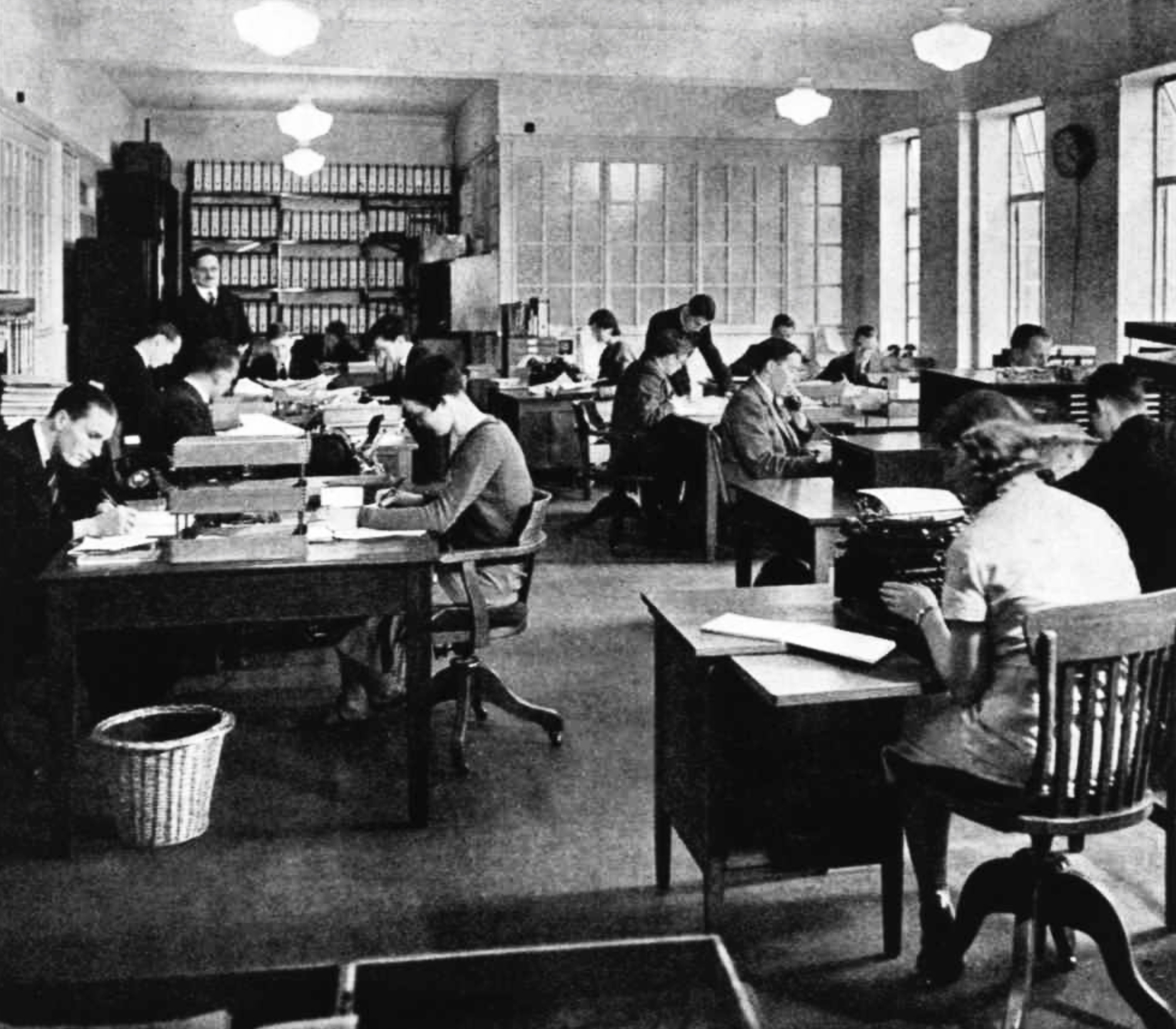 A busy office with men and women working around double-sided desks