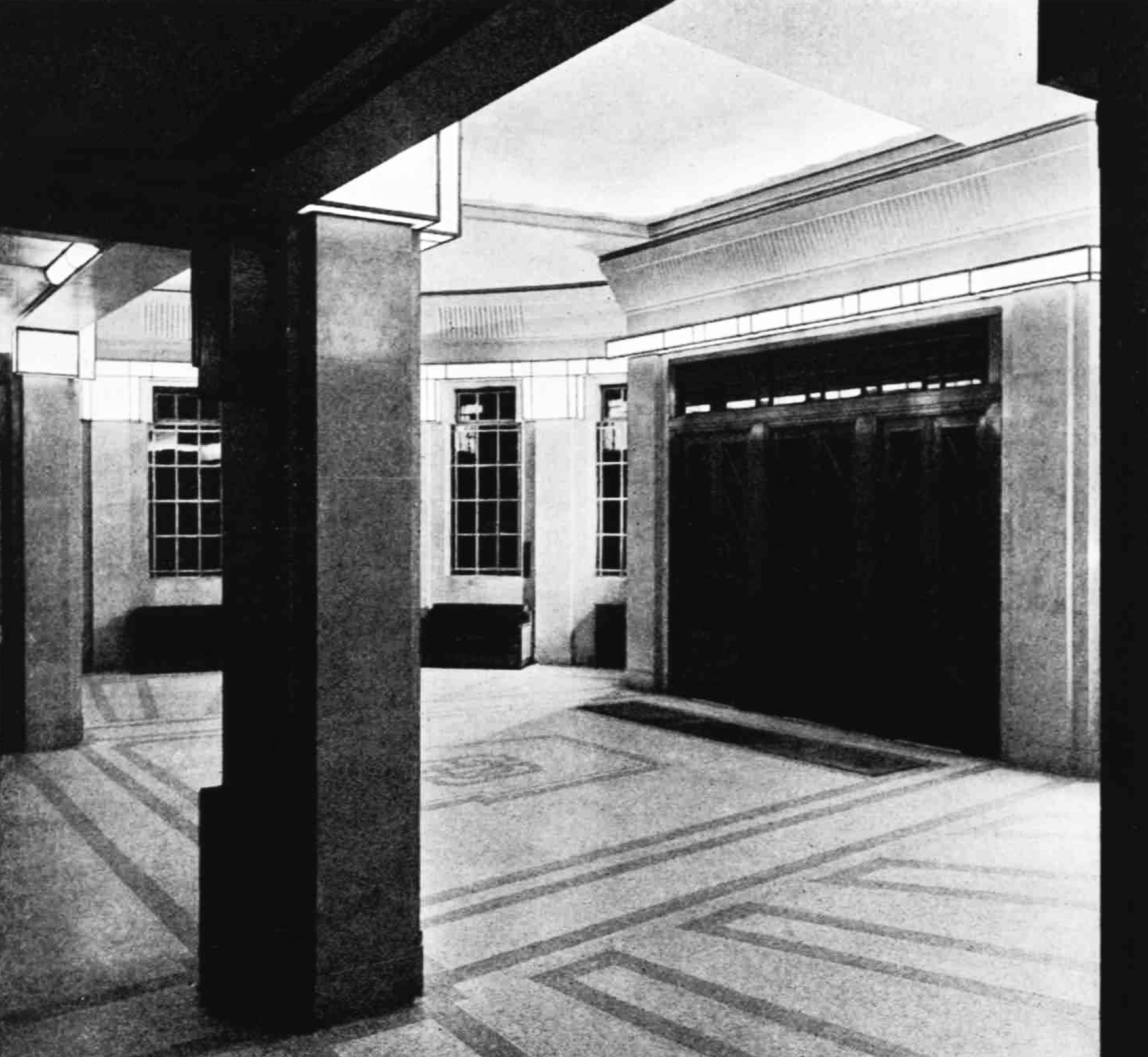 A wide space with square pillars and a mosaic floor